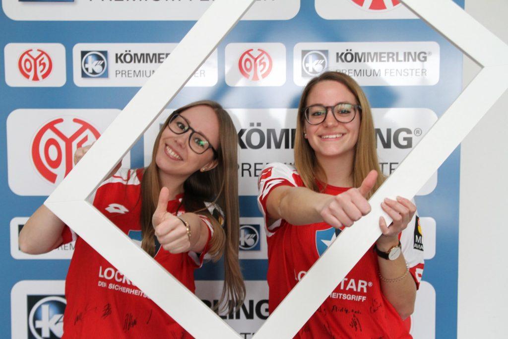 Zwei profine Studentinnen im Mainz 05 Trikot schauen durch ein Fensterprofil