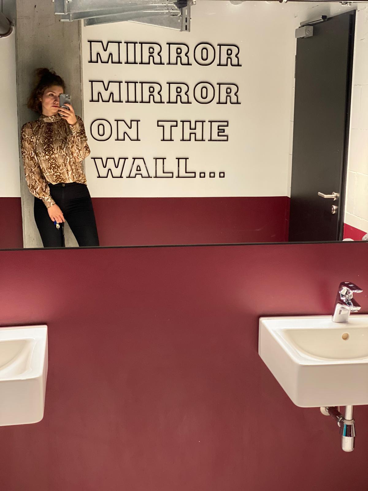 """Mitarbeiterin, daneben eine Wand auf der steht """"Mirror mirror on the wall..."""""""