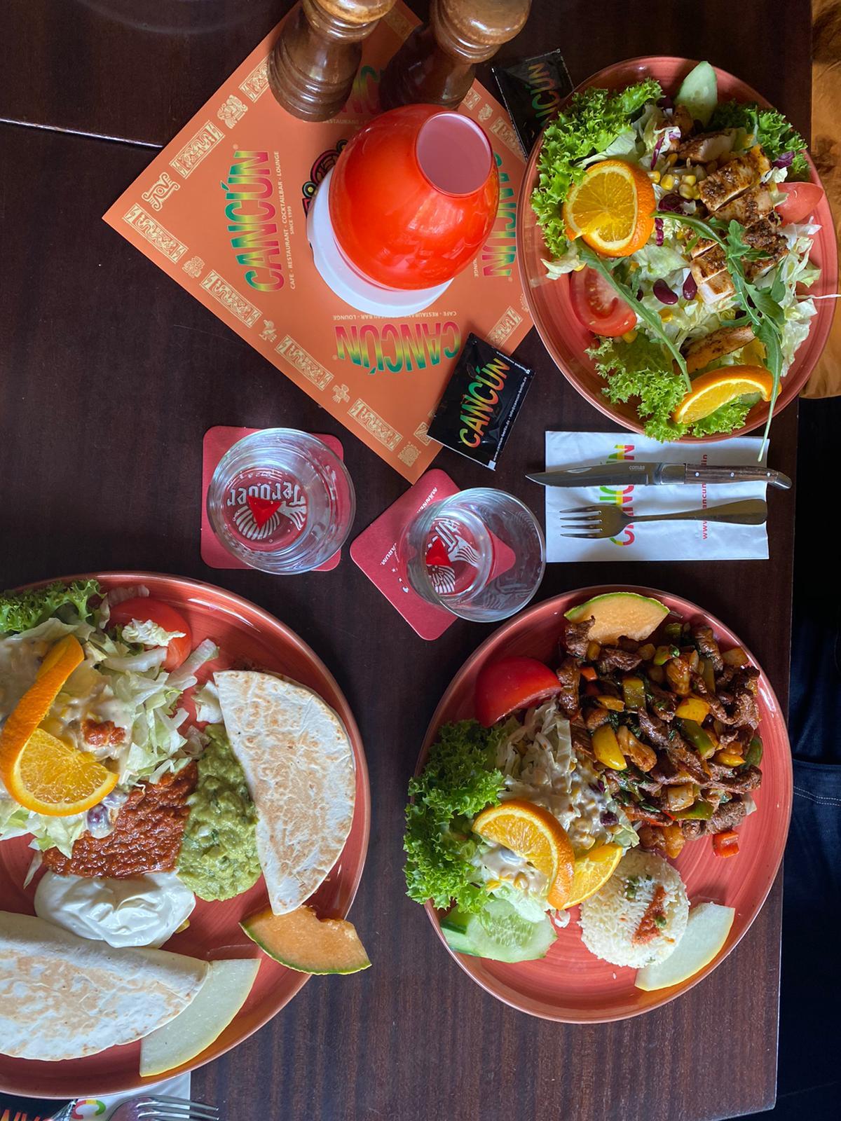 Gedeckter Tisch mit 3 vollen Tellern.