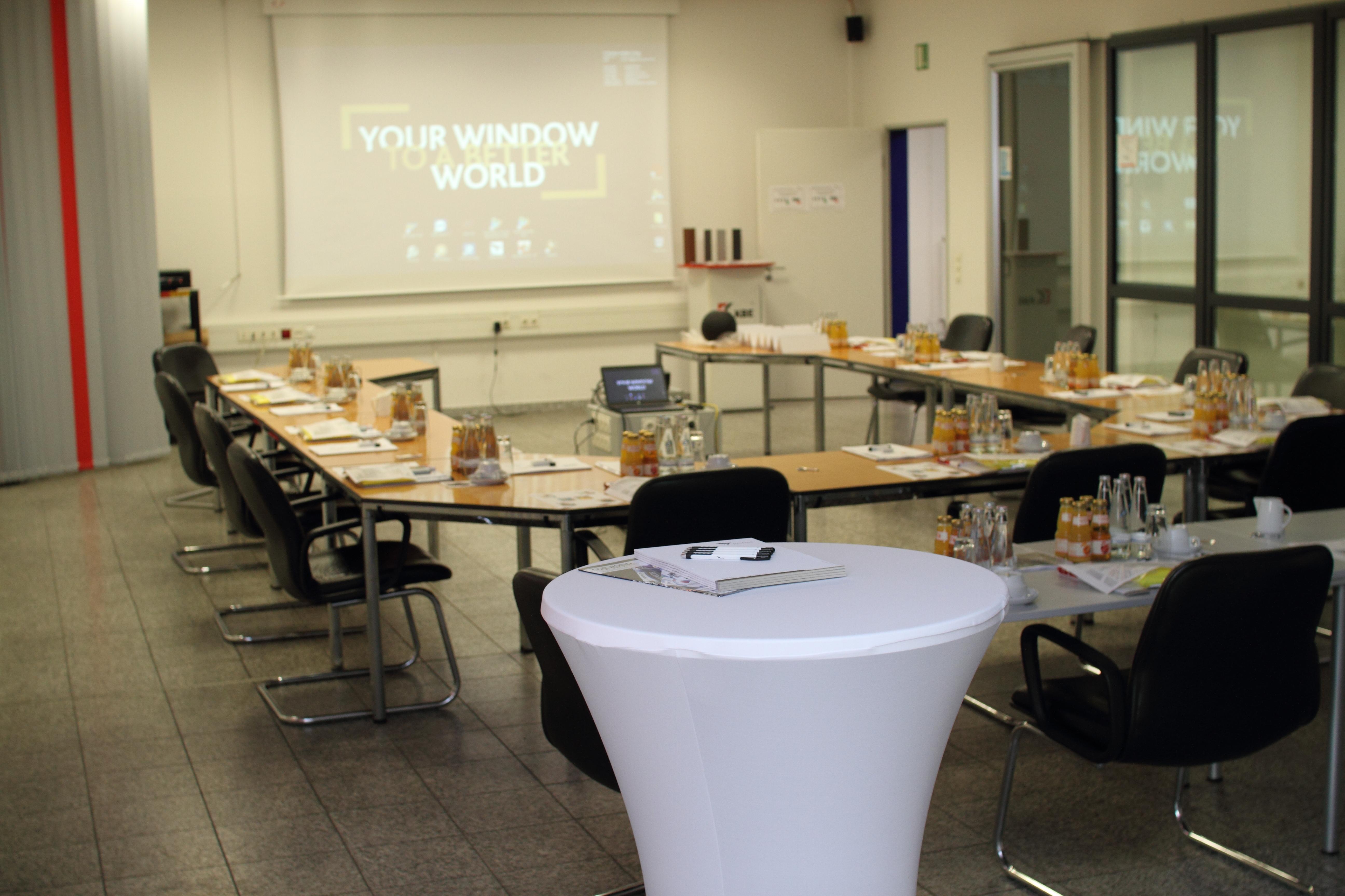 Vorbereiteter Schulungsraum in Berlin mit Startseite des profine Desktops auf der Leinwand.