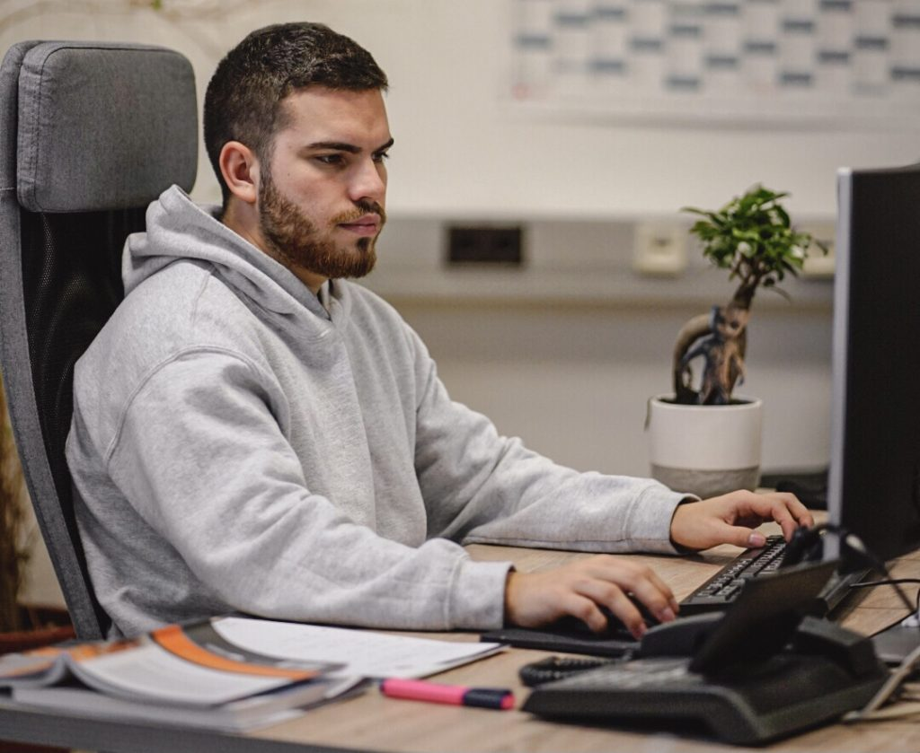 Unser Dualer Wirtschaftsinformatik Student Max sitzt an seinem PC-Arbeitsplatz.