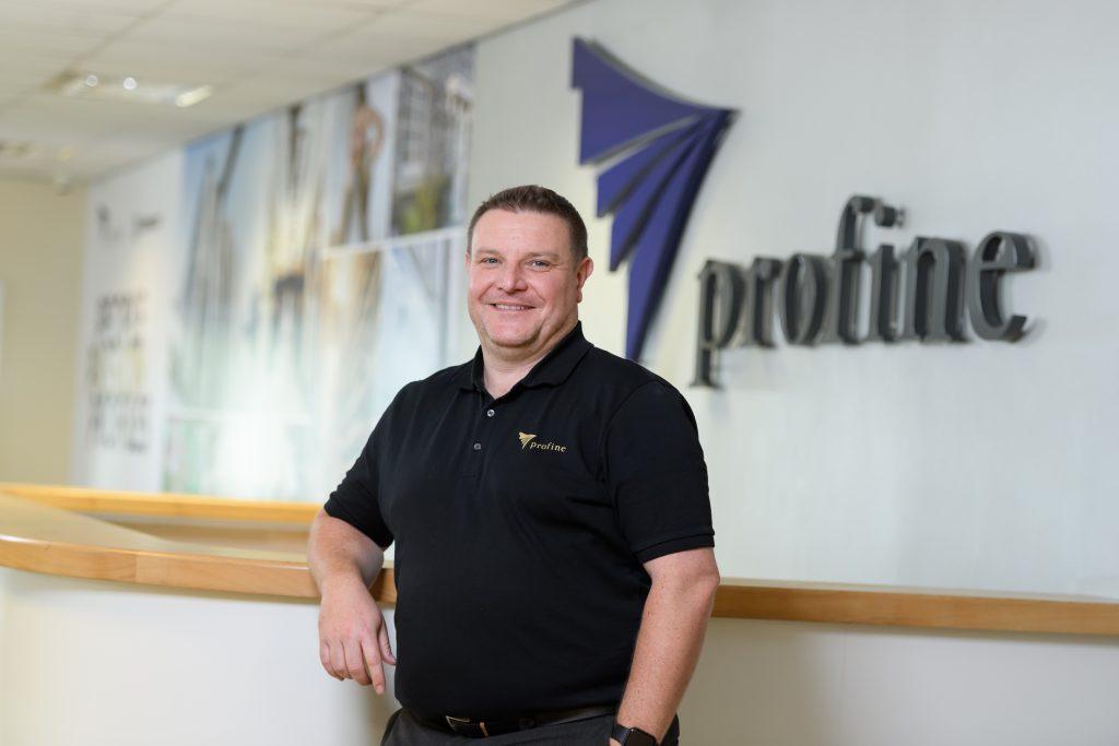 Profine Mitarbeiter Gareth Jones vor dem profine Logo.