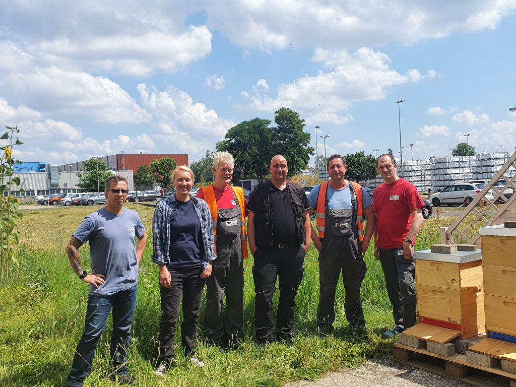 6 Mitarbeiter der profine auf der Wiese neben einem Parkplatz.
