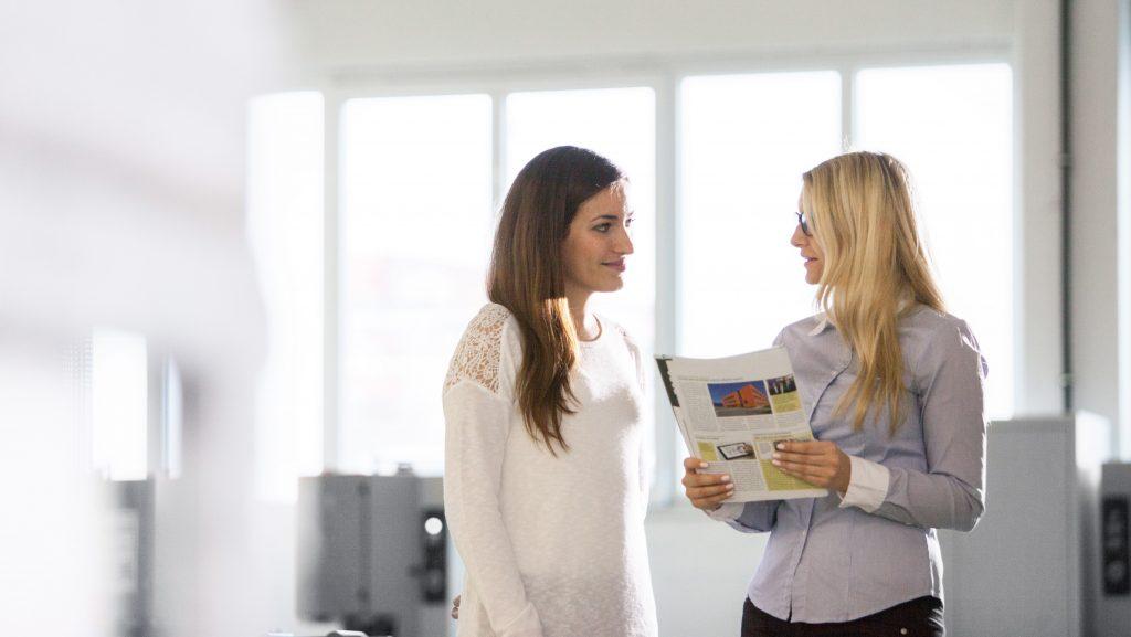 Zwei profine Kolleginnen betrachten gut gelaunt die Mitarbeiterzeitschrift.
