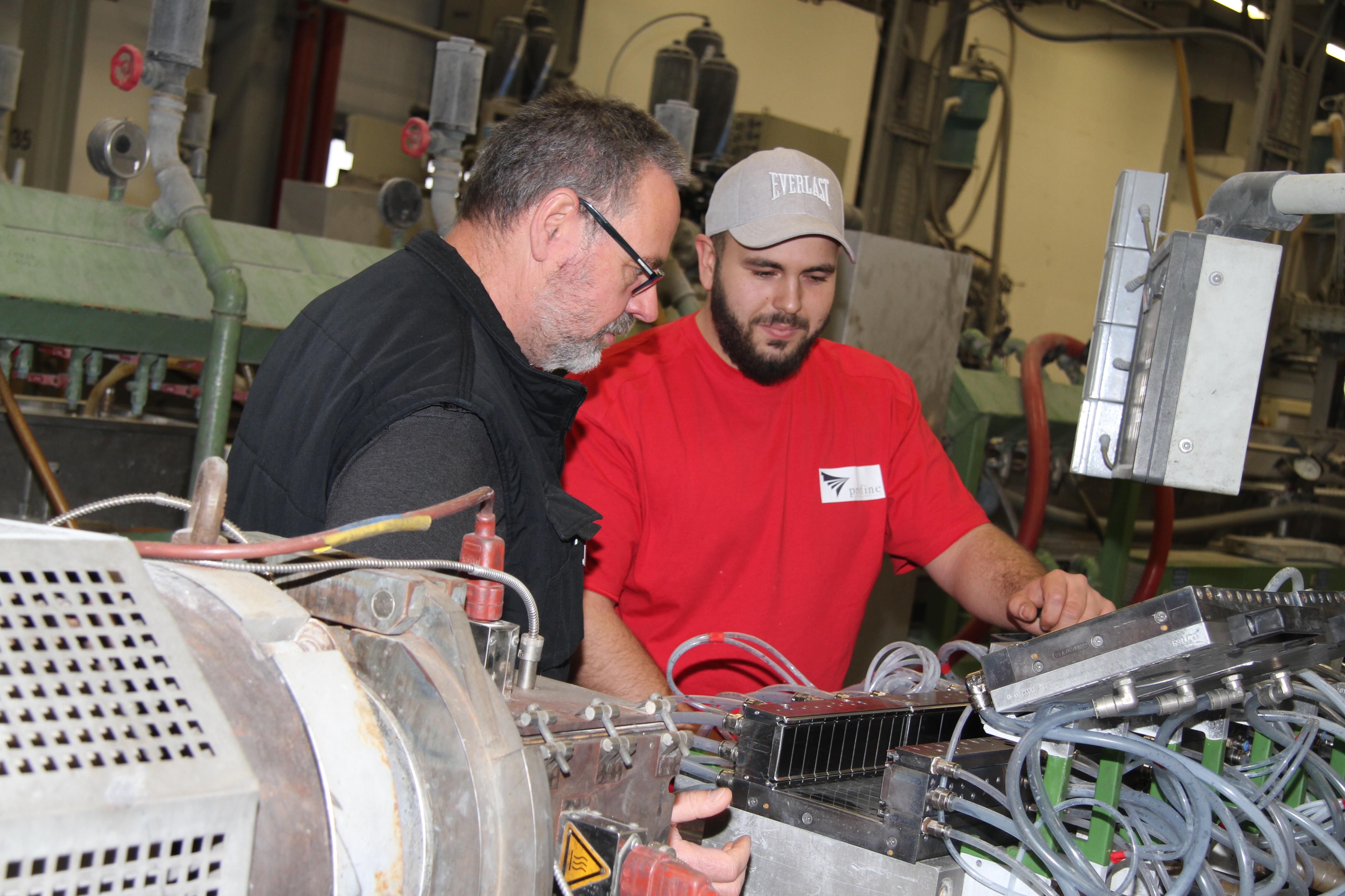 Ausbilder Michael Peukert und Verfahrensmechaniker Mert Savac vor einer Maschine.