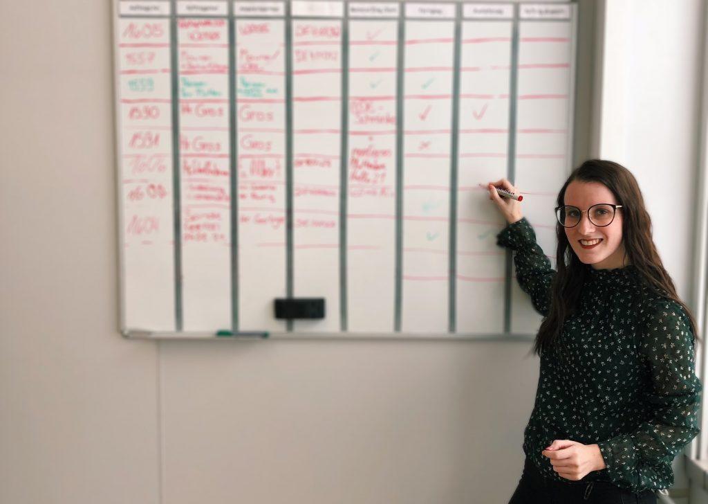 Unsere Auszubildende Jasmin, Geschäftsführerin unserer Juniorenfirma, mit Stift an einem beschrifteten Whiteboard