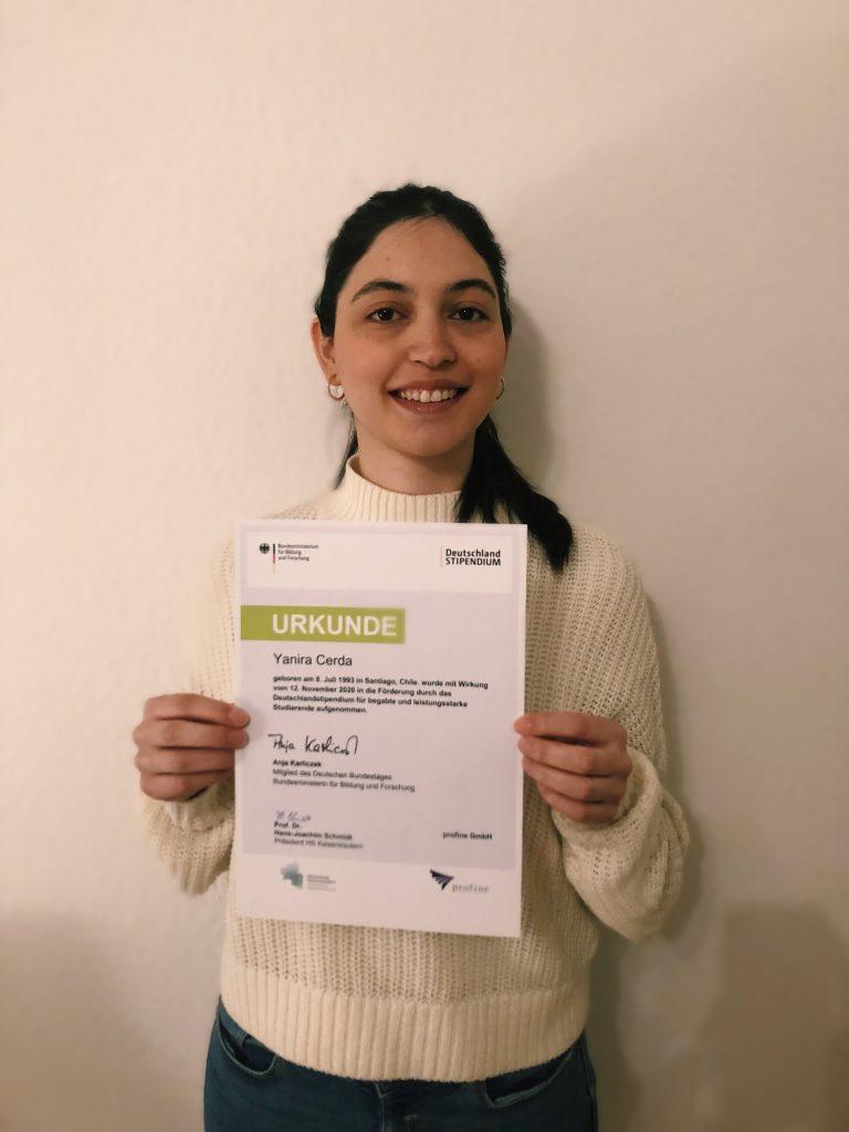 Yanira, die Stipendiatin der profine lächelnd mit ihrer Urkunde des Deutschlandstipendiums in den Händen.