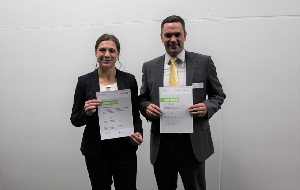 Übergabe des Deutschlandstipendiums im Jahre 2019. Andreas Langner und die Stipendiatin halten eine Urkunde in den Händen.