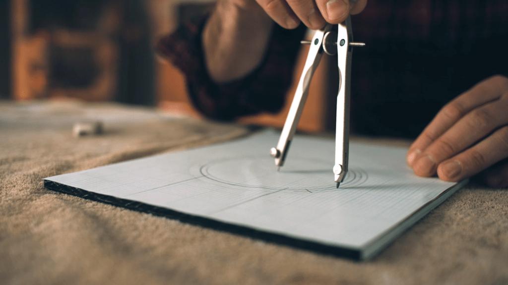 Mann zeichnet mit einem Zirkel mehrere Kreise auf ein Blatt.